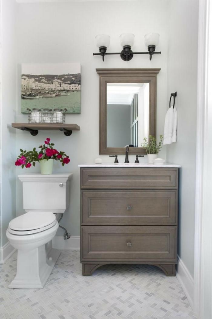 laminas vintage, baño clásico pequeño, mueble de madera oscura, decoración con flores y cuadro con paisaje de ciudad en la costa