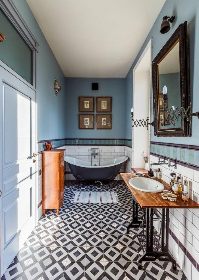 laminas decorativas,baño largo y estrecho, paredes en blanco y azul, espejo grande, bañera. cuadro cuadros pequeños con marcos de madera