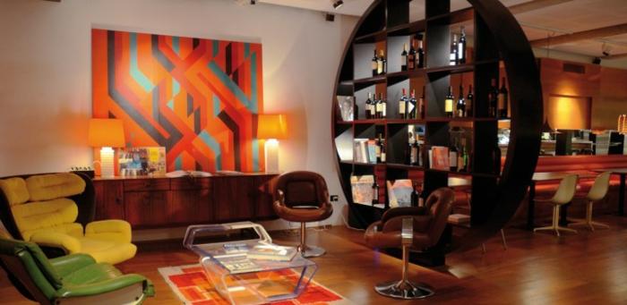 sillas vintage, salón colorido, decoración en naranja en la pared, sillas vintage en verde y amarillo, estantería de madera en forma oval