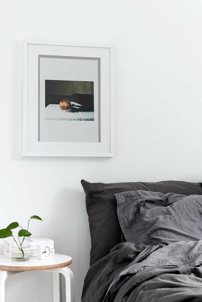 ideas para decorar una habitacion, habitación en estilo minimalista, sábanas en gris, mesa de madera pequeña. pintura moderna en la pared