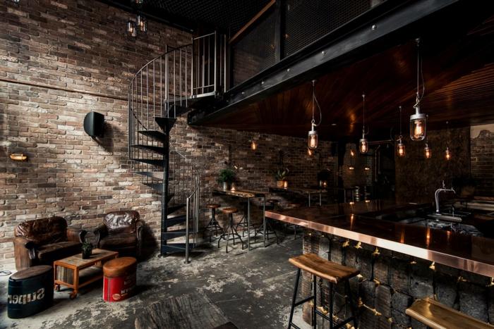 escaleras, decoracion industrial, salon y comedor con escalera de metal tipo caracol, pared de ladrillo, suelo con aspecto desgastado, lamparas colgantes