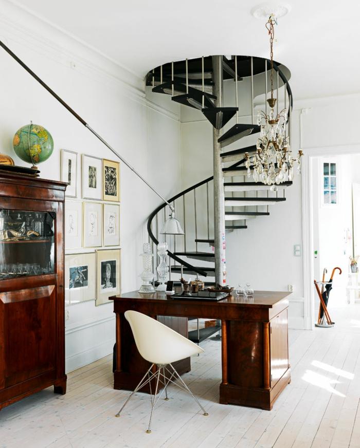 escaleras, salon con escritorio de madera, suelo con tarima blanca, escaleras negras de caracol con barandilla, lampara de araña