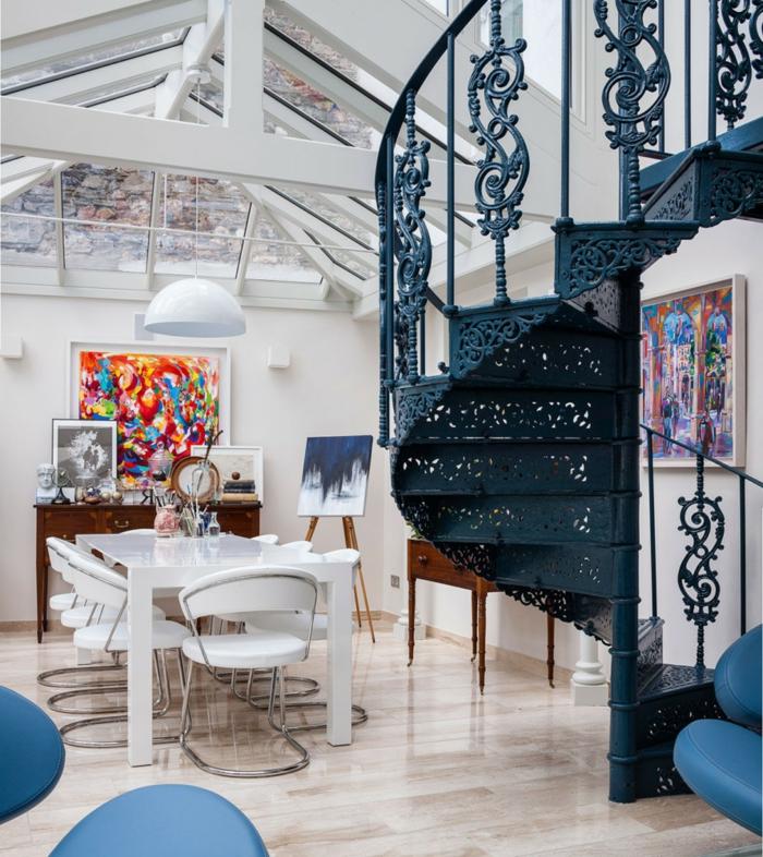 escaleras de interior, salon moderno con buhardilla, mesa blanca, pinturas grandes en la pared, escalera metalica de caracol, barandilla azul con adornos