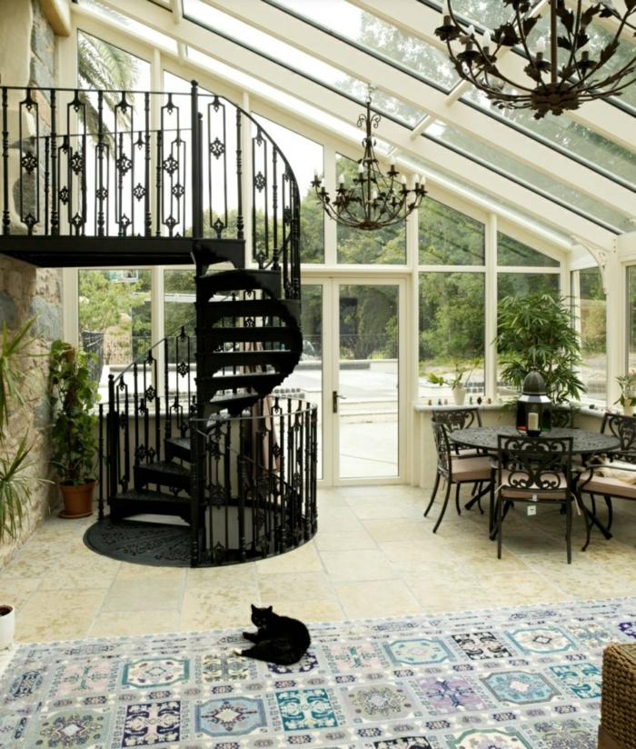escaleras de interior, salon de casa rustica con buhardilla, ventanales, suelo de baldosas, alfombra con gato negro, lampara de araña, escalera negra de metal tipo caracol