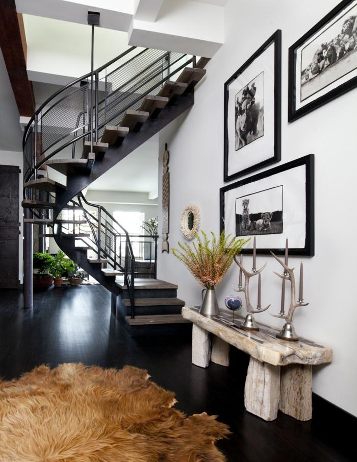 escalera caracol, salon moderno con elementos rusticos, banco de madera, fotografia en blanco y negro enmarcadas, escalera de caracol metalica negra, alfombra de piell peluda