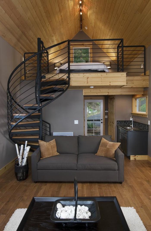 barandillas escaleras, salon con techo triuangular con tarima, sofa gris con cojines, balcon interior con cama, escalera de caracol negra de metal