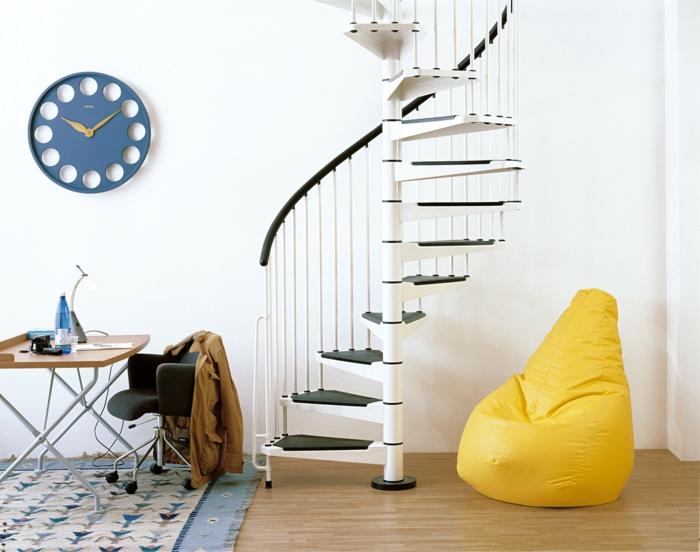 excalera metalica, salon minimalista con escritorio y puf amarillo, reloj de pared azul, escalera de caracol prefabricada en blanco y negro