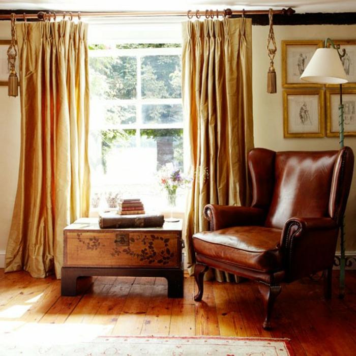 decoración vintage, salón decorado en estilo clásico con grande sillón de piel y caja de madera, cortinas de satén en color ocre