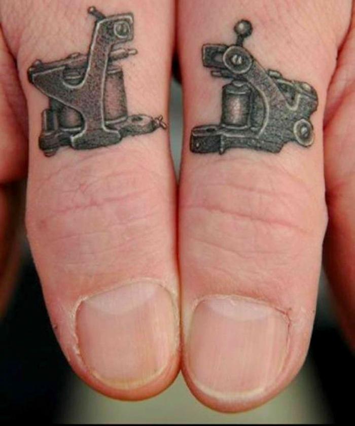 tatuajes en la mano, manos de hombre con tatuajes de máquinas antiguas negras en los dos pulgares