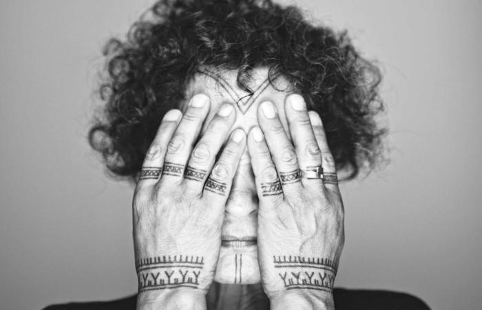 tatuajes en la muñeca, hombre con tatuajes en la cara y las manos, todos los dedos con tatuaje de anillo, símbolos tribales, foto en blanco y negro