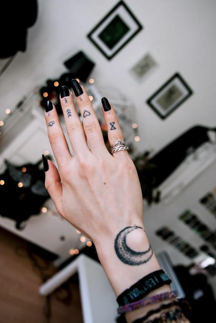 ideas para tatuajes, mano de mujer con uñas largas negras, tatuaje de luna en la muñeca, corazón y flecha en los dedos