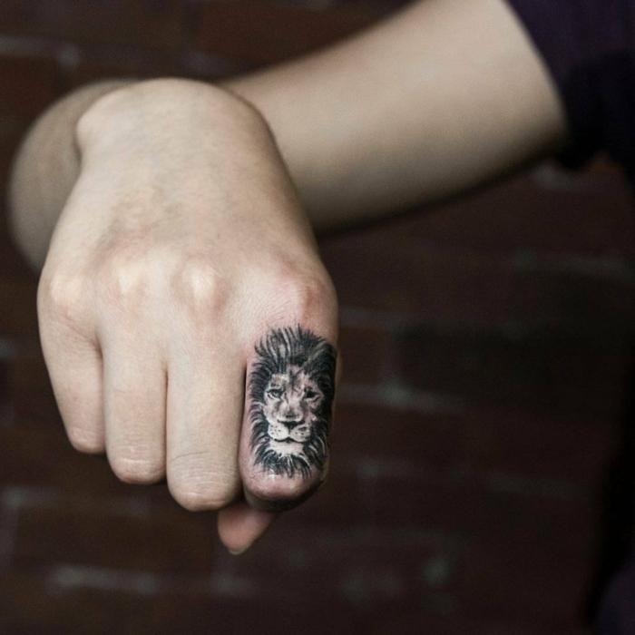 tatuaje corazon, dedo índice con tatuaje cabeza de león detallado en la falanga, propuesta para hombres y mujeres