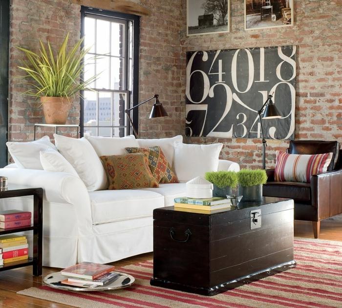 revestimiento paredes, salón pequeño con ventana grande, sofá blanco y mesa hecha con caja de madera, parede de ladrillo visto con cuadros
