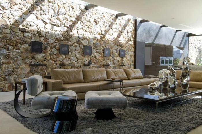 pared ladrillo, salón grande con sofá tapizada con piel, pared de piedra con cuadros en blanco y negro, ventanas en el techo