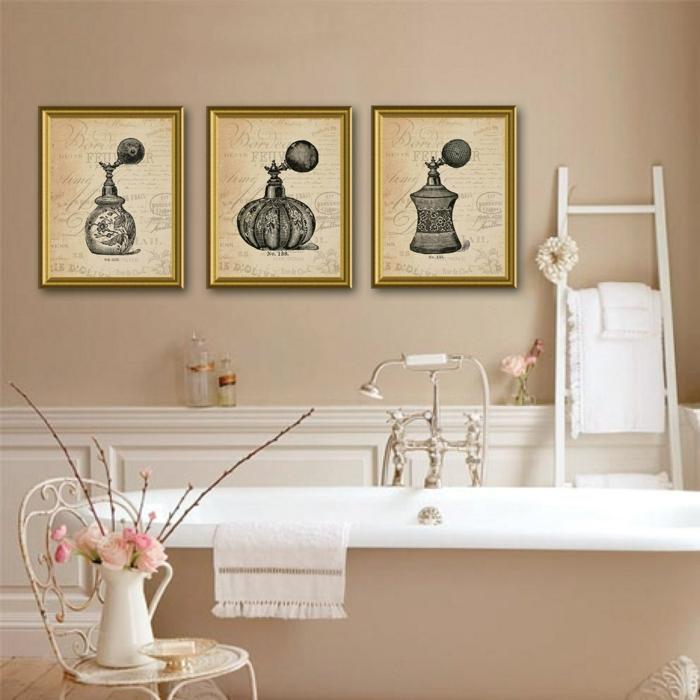 cuadros para baños, baño en beige estilo vintage, bañera, tres cuadros vintage con marcvos dorados, botellas de perfumes antiguos