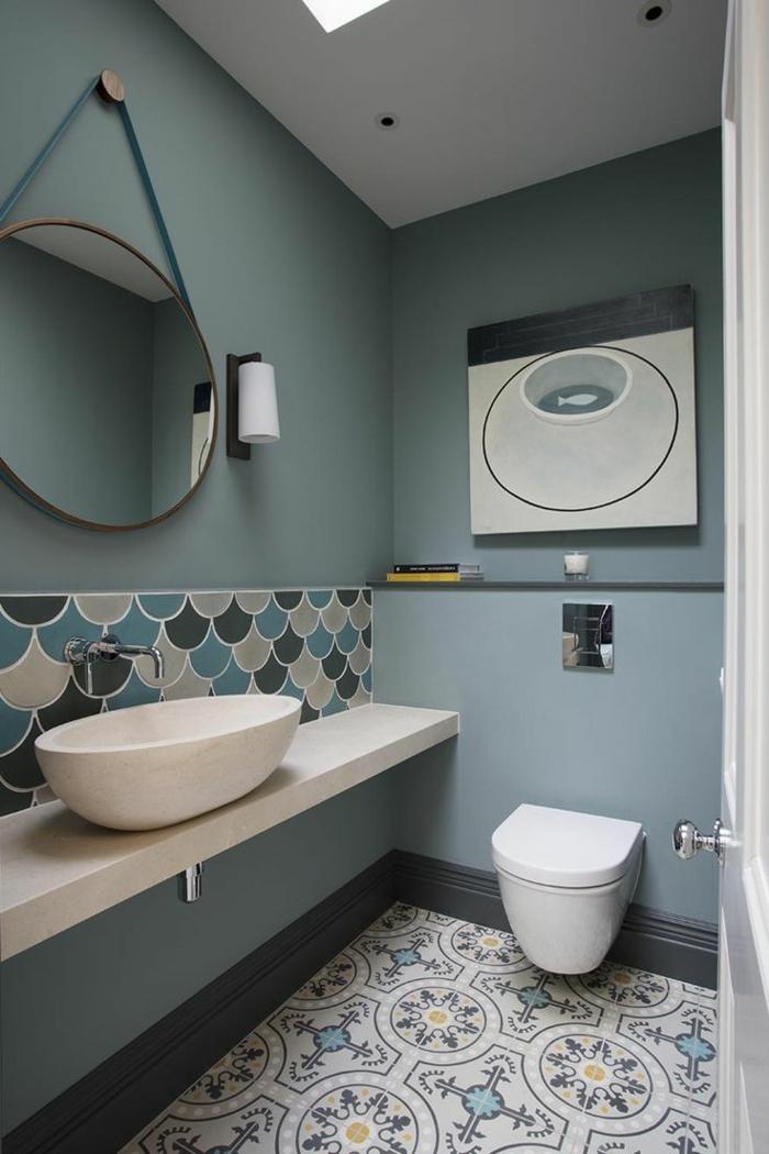 cuadros decorativos, baño moderno en blanco y azul, espejo redondo, pintura abstracta con una pez, suelo con azulejos