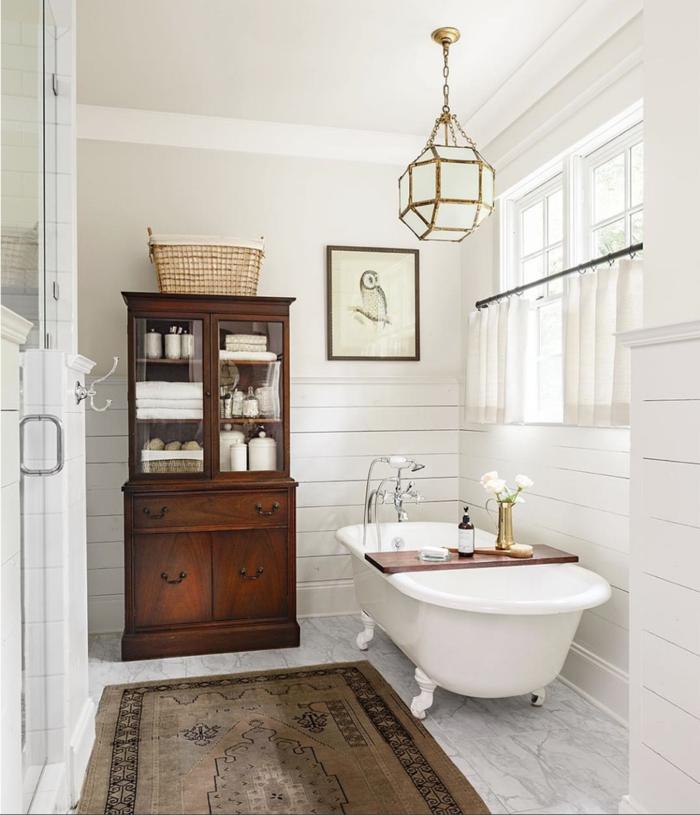 cuadros decorativos, baño pequeño con bañera y armario, decoración de pared con imagen de buho enmarcada, tapete y lámpara colgante