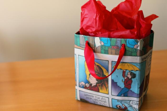 manualidades con carton, bolsita de regalo de hecha con hojas de comic viejo con asa de cinta roja y papel de rseda rojo