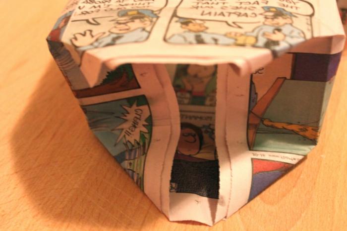 manualidades con carton, como formar el fondo de una bolsita de regalo reciclada hecha con papel de periódico vieja