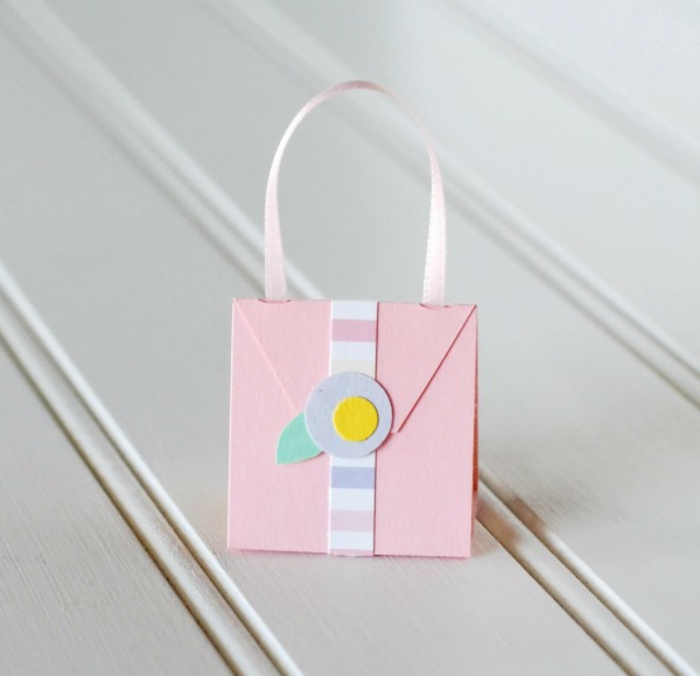 manualidades con cartulina, mini bolsa hecha con cartulina rosada y cinta decorativa, tutorial paso a paso