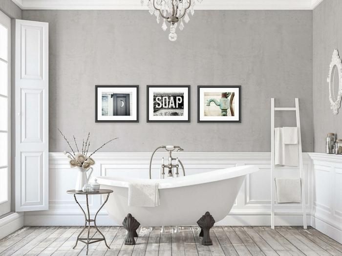 cuadros para baños, baño grande con suelo de tarima, bañera de lujo, paredes gris decoradas con cuatro lfotos laminadas, ventana grande