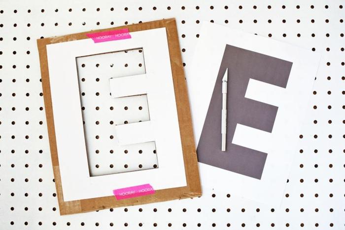 manualidades con carton, primer paso para hacer guirnalda de cartón reciclado y lentejuelas, cortar letras con un molde