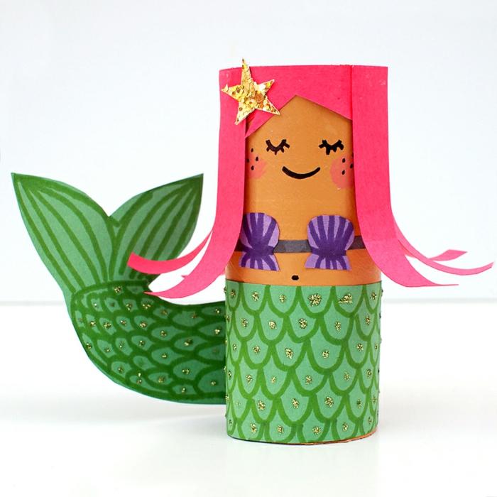 manualidades con papel de periódico, sirenita con pelo rosado hecha con cono de papel higiénico reciclado