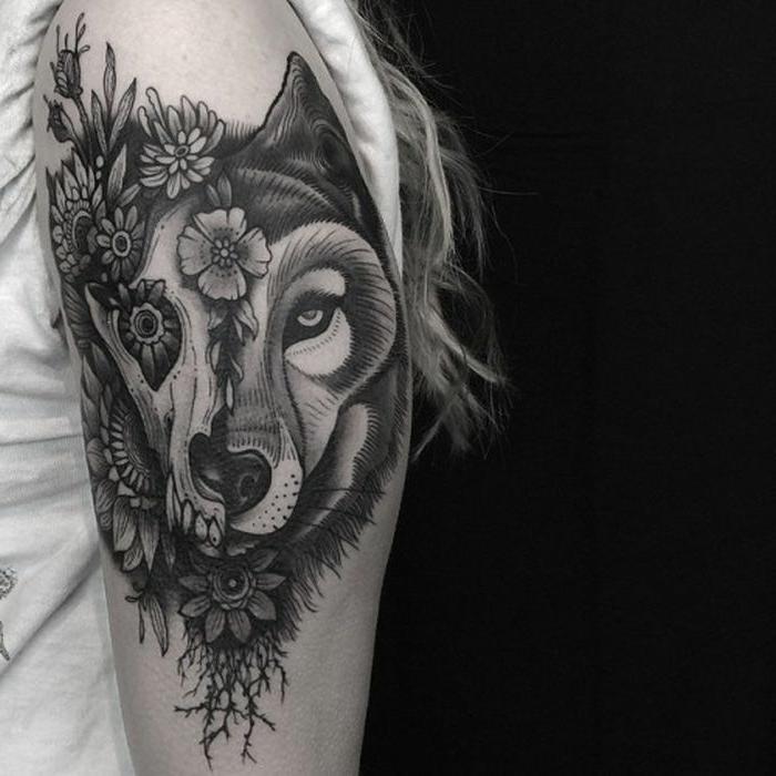 tatuajes de animales, foto en blanco y negro, mujer con pelo largo rubio, tatuaje en el brazo, cabeza de lobo en estilo realista y estilo mexicano