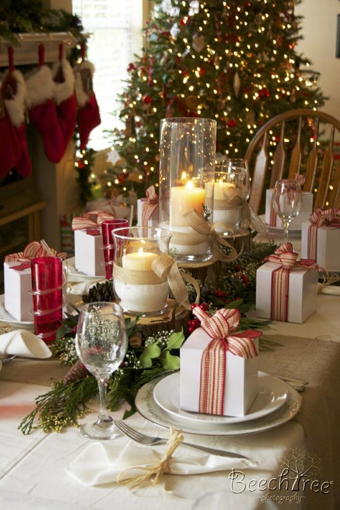 centro de mesa navideño, centros de mesa con velas y ramas de pino, paquetes en blanco y rojo en los platos