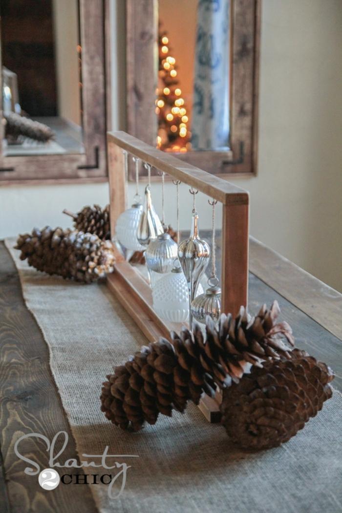 centros de navidad, ornamentos de cristal para el árbol de navidad colgados en un marco de madera, piñas decorativas
