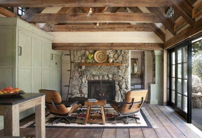 cabañas de madera, interior agogedor con chimenea de leña con revestimiento de piedra, sillones, suelo y mesa de madera