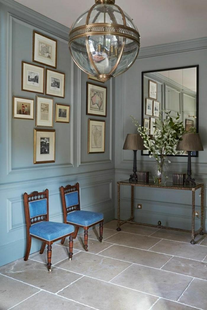 recibidores baratos, vestíbulo grande con suelod e baldosas, sillas bajas tapizadas en azul, espejo gramde, decoración con fotos en blanco y negro, la,para colgante
