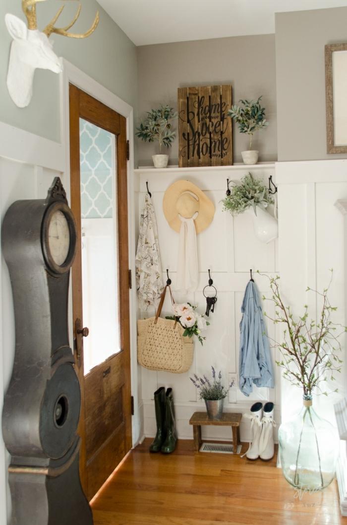 recibidores pequeños, recibidor vintage con reloj de metal antiguo, pared con cabeza de ciervo artificial, percha con sombrero, ropa y bolsa