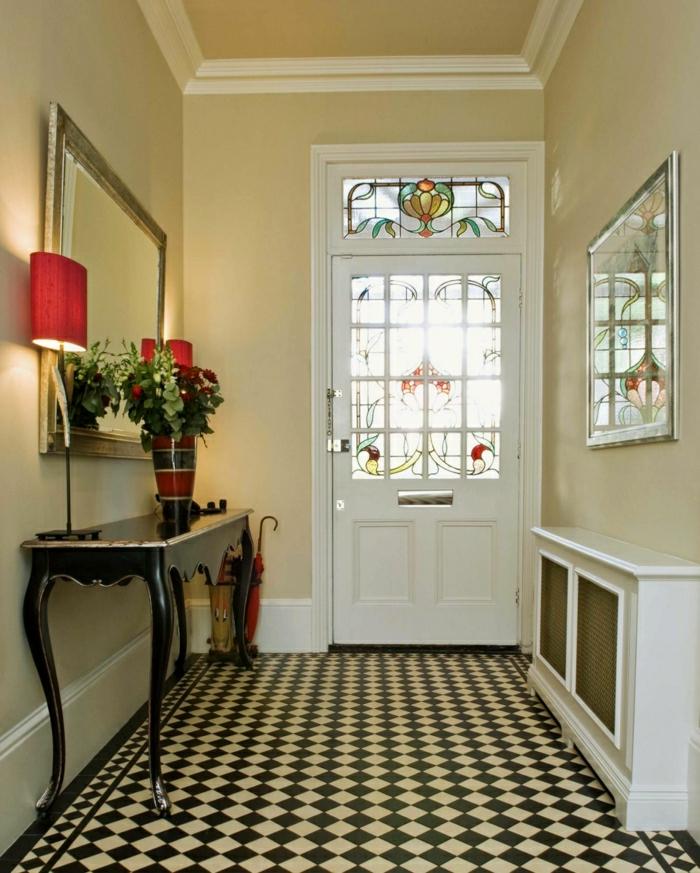 recibidores pequeños, recibidor en el pasillo, suelo con rombos, aparador negro, lámpara roja, jarrón con flores, espejo gramde