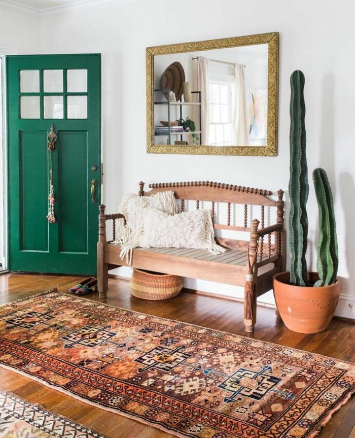 recibidores modernos, recibidor grande estilo rústico con banco de madera, espejo y cactus grande, alfombra y puerta verde