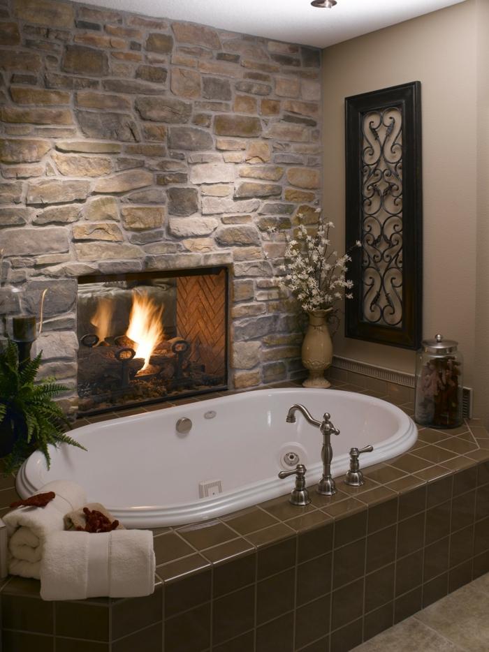 pared de piedra, decoración de baño con chimenea encendida y bañera, pared de piedra rústica y flores
