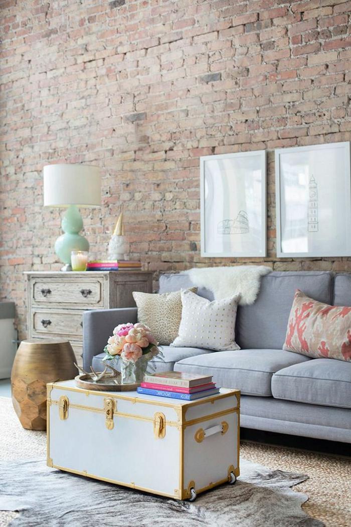 pared de piedra, salón en colores pastel, sofá con cojines, caja convertida en mesita, pared de aldrillo con aspecto desgastado