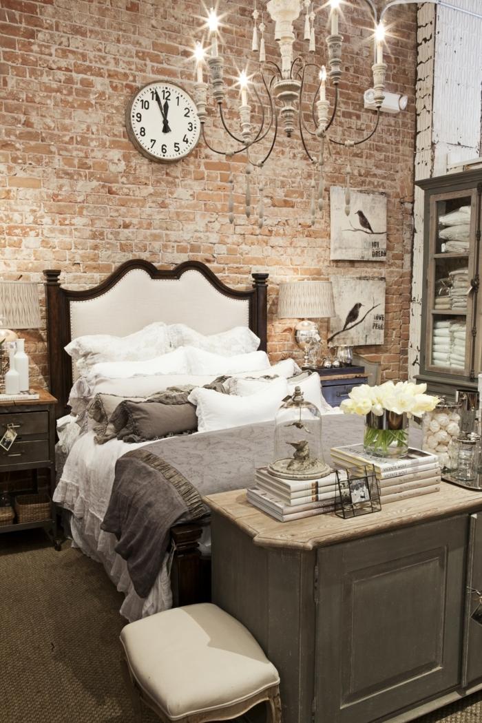 pared de piedra, dormitorio con cama doble, estilo de decoración mixto, lámpara de araña, techo alto, pared de ladrillo con reloj