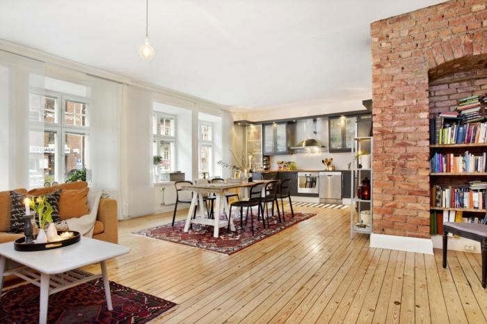 pared de piedra, cocina abierta al salón y el comedor, suelo de tarima, ventanales grandes, pared de ladrillo con nicho con librería
