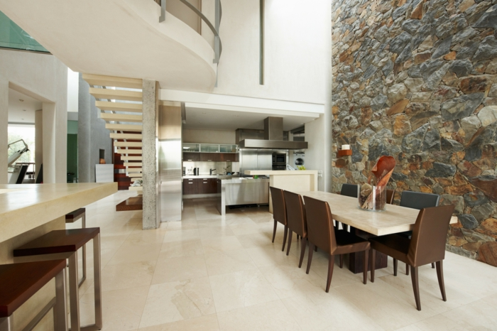 pared de piedra, casa moderna con dos pisos y escaleras, cocina abierta al comedor con mesa rectangular, pared alta de piedra decorativa