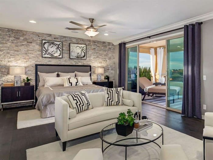 ladrillo caravista, dormitorio moderno en blanco, negro y gris, terraza grande con tumbonas, pared de piedra, lámpara ventilador