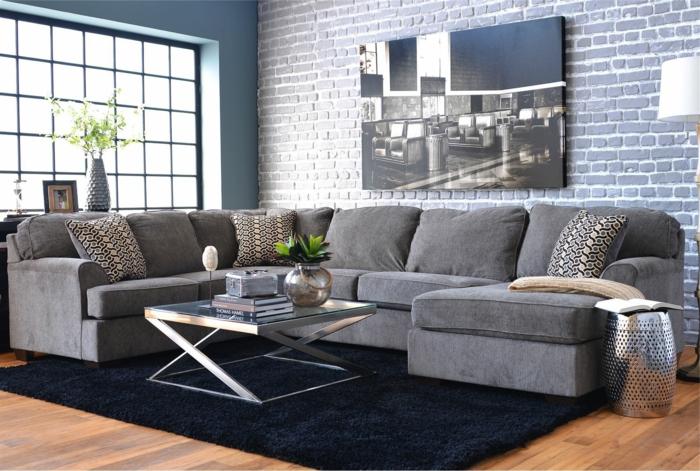 panel piedra, salón decorado en gris con ventanal y mucha luz natural, sofá con cojines, pared de ladrillo pintado con foto en blanco y negro