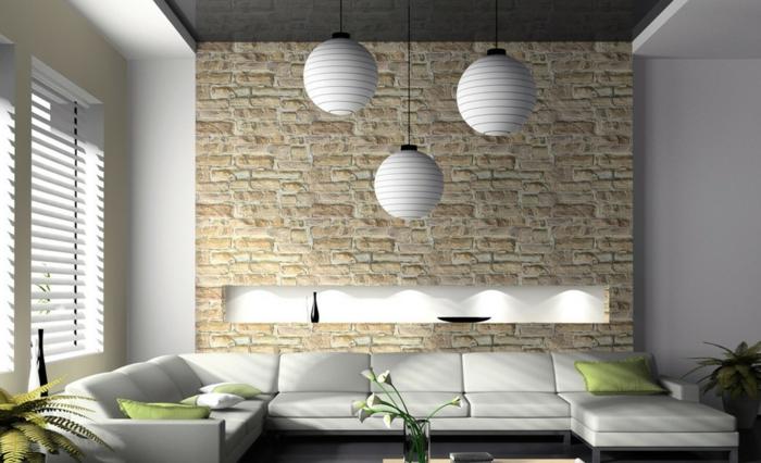 panel piedra, salón pequeño, sofá blanca con cojines verdes, lámparas colgarntes, ventana con estores, panel de piedra con nicho
