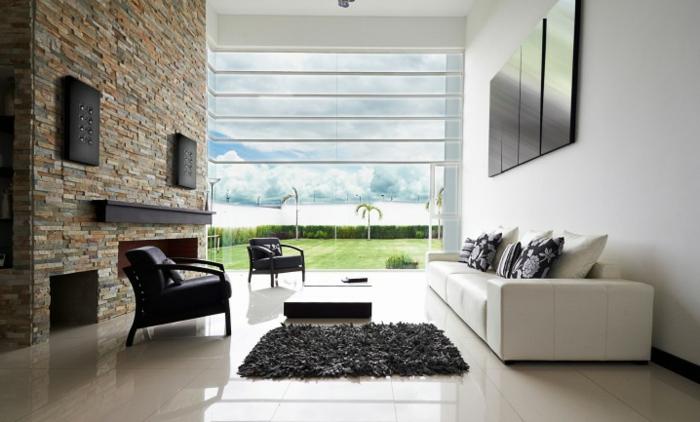 panel piedra, salón moderno con gran ventanal, techo alto, pared de piedra con decoraciones en negro, sofá blanco de piel