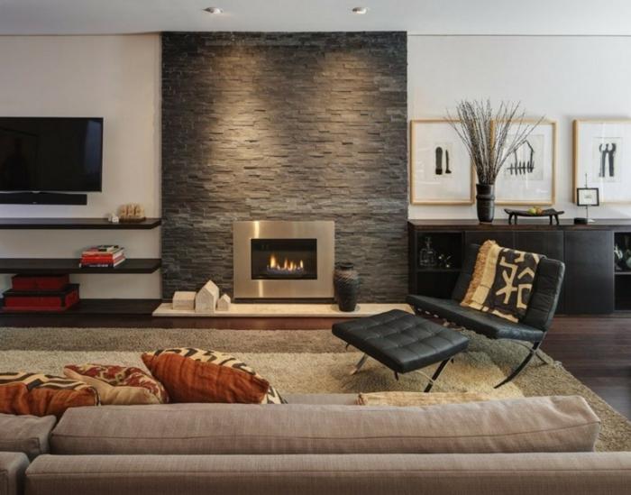 ladrillo visto,salón moderno con chimenea encendida integrada en panel de piedra, sofá beige y sillón de piel negro