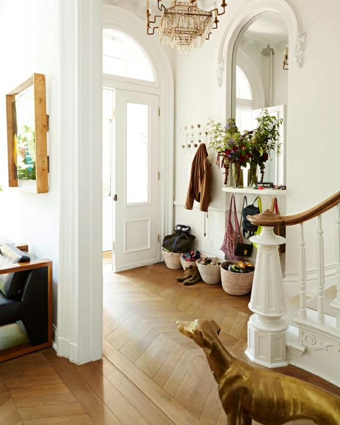 recibidores originales, recibidor grande, paredes altos blancos, lámpara de araña, estatua de perro en dorado, espejo grande, canastas