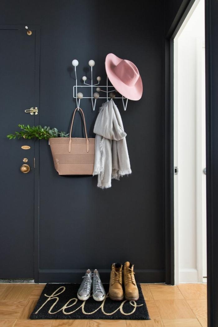 muebles recibidor, estilo minimalista, pared negra, felpudo con hello, percha blanca con sombrero, bufanda y bolsa