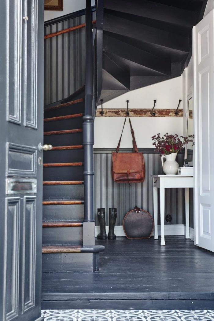 recibidores, recibidor pequeño bajo las escaleras, percha vintage con bolsa de puiel, mesita blanca con jarra de flores