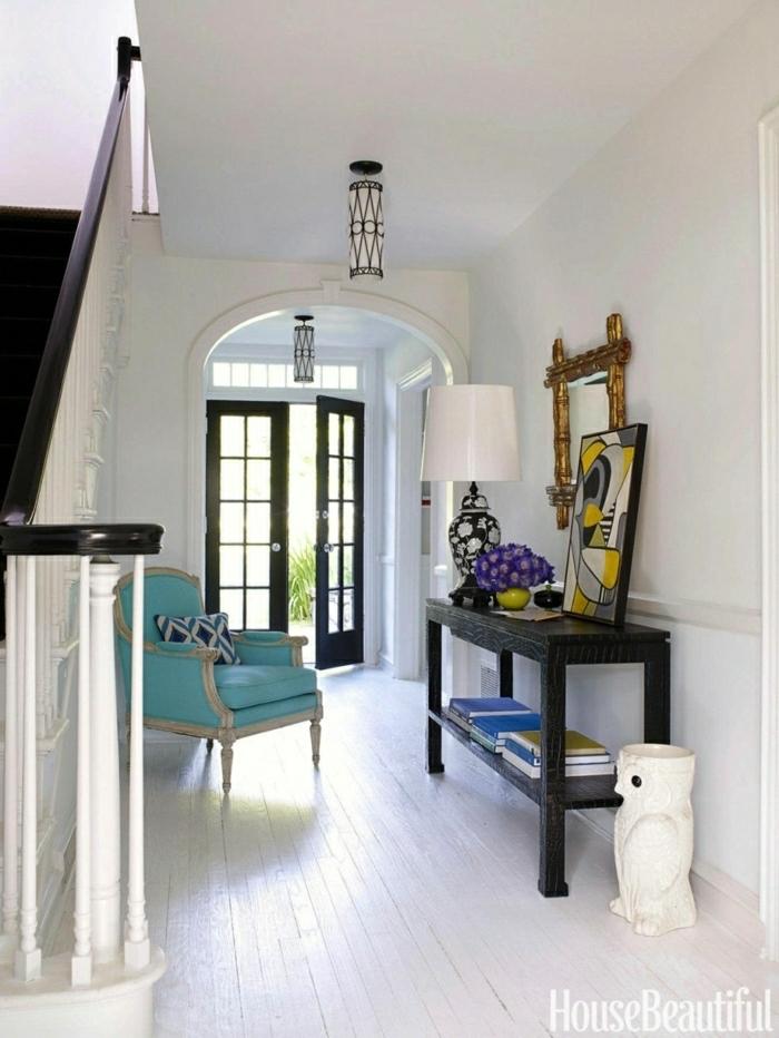 recibidores, recibidor grande con apardor negro, espejo con marco dorado, sillón clásico azul, suelo de tarima blanca