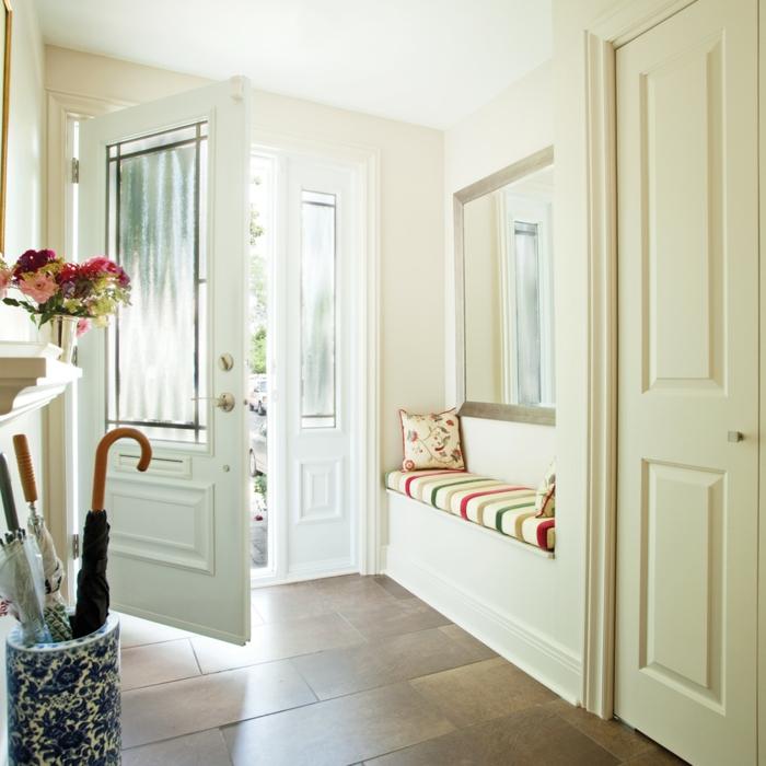 muebles de entrada, recibidor en blanco, banco con colchoneta y cojines, suelo de baldosas, espejo grande en la pared